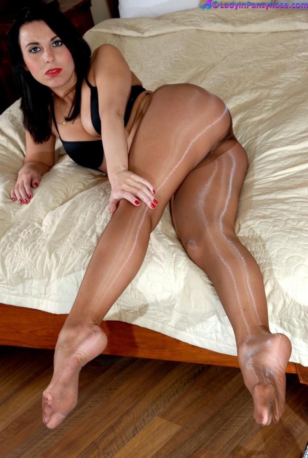 блестящие колготки коричневые на красивой брюнетки лежит на кровати на боку в черном лифчике