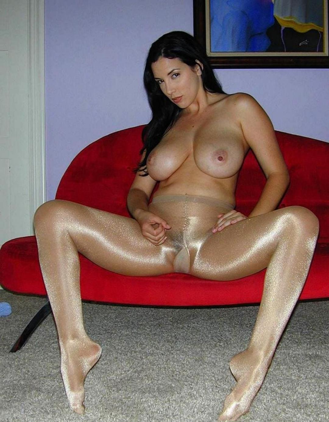 девушки в блестящих колготках широко раздвинула ноги голая брюнетка с длинным волосом сидит на красном мини диване
