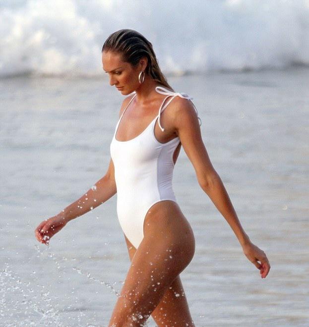 Кэндис Свейнпол в белом купальнике по колено в воде идет размахивая руками