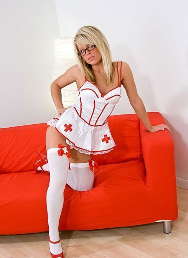 Сексуальная блондинка позирует в костюме для медсестры  стоя на левом колене на красном диване в белых чулках и очках, красные туфли на каблуке