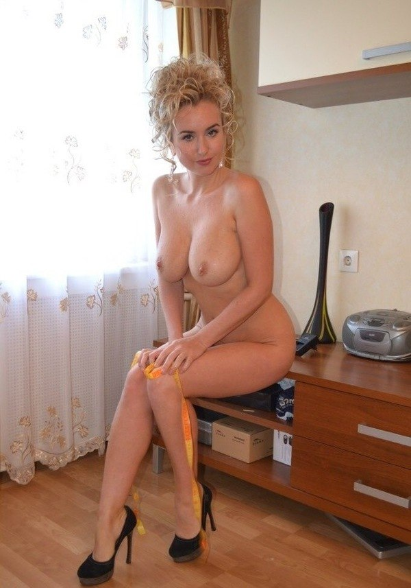 Красивая голая блондинка в туфлях на каблуке сидит на тумбочке