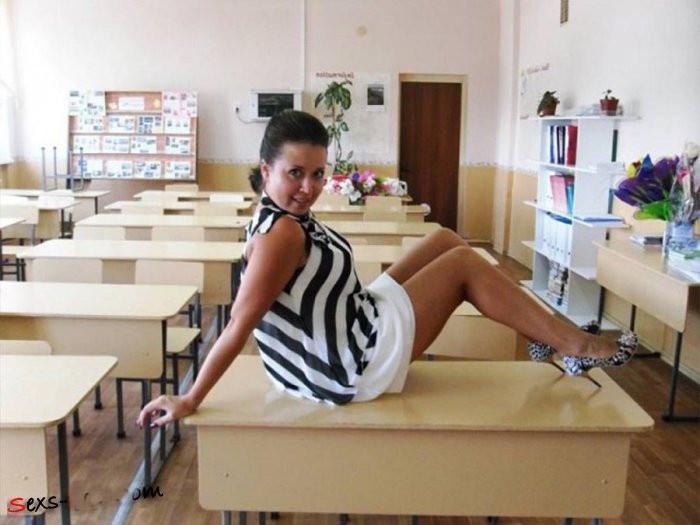 Фото русских учительниц частное сидит на парте, здрав платье, ноги согнуты в коленях, туфли на высоком каблуке
