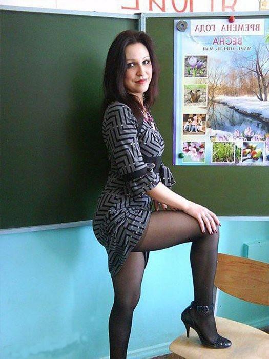 Фото русских учительниц стоит возле школьной доски, одна ножка на стуле, черные колготки, платье задрано, показывает свои ножки в туфлях на каблуке