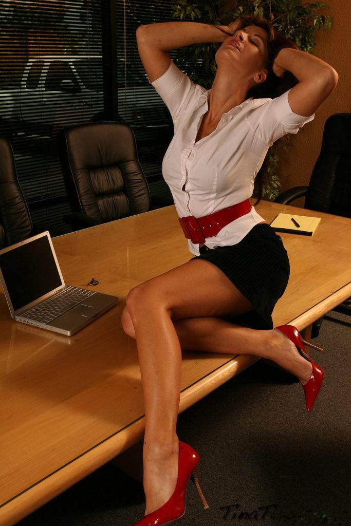 Эро фото секретарши сидит на столе в белой кофточке, широкий кожаный пояс, короткая черная юбка, красные туфли на высоком каблуке, руки подняты на голову, голова запрокинута назад