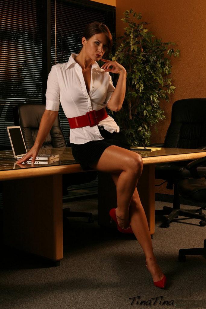 Красивые секретарши фото сидит на столе в белой рубашке, короткой черной юбке, красных туфлях на каблуке, стройные ножки
