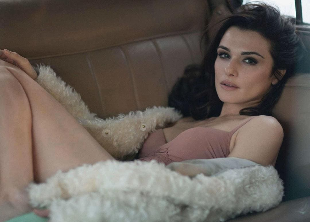 Рэйчел Вайс фото на диване лежит в белом расстегнутом полушубке, ножки согнула в коленях
