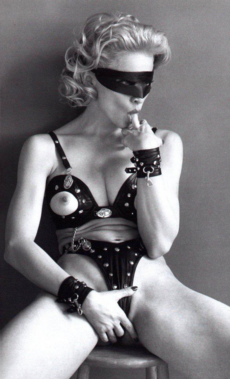 Мадонна фото горячие фото в костюме для БДСМ с маской на лице сидит, палец правой руки сосет, левой рукой держится за пизду