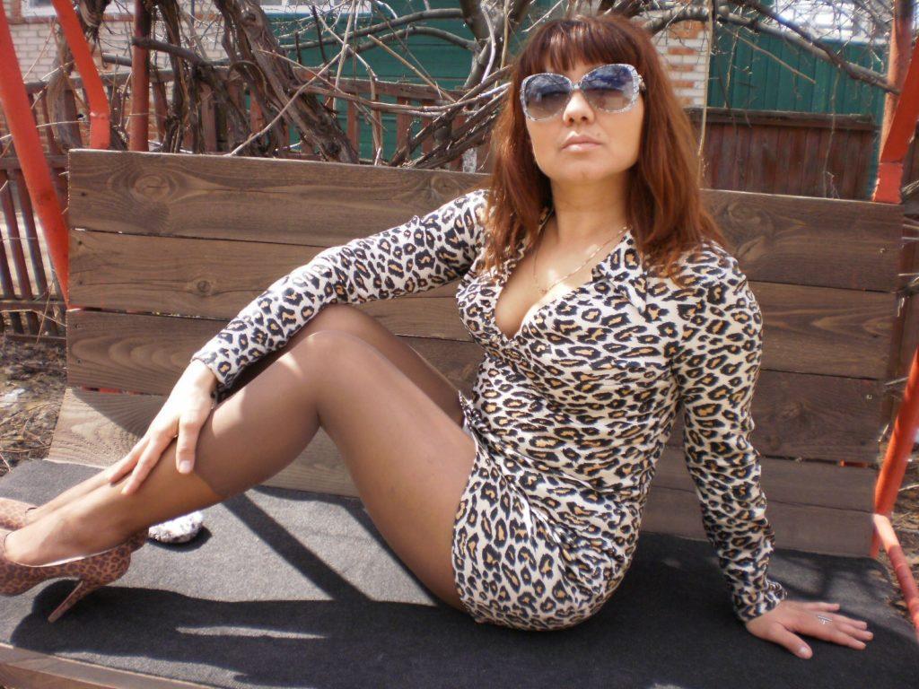В леопардовом платье сидит на лавочке показывает свои ножки