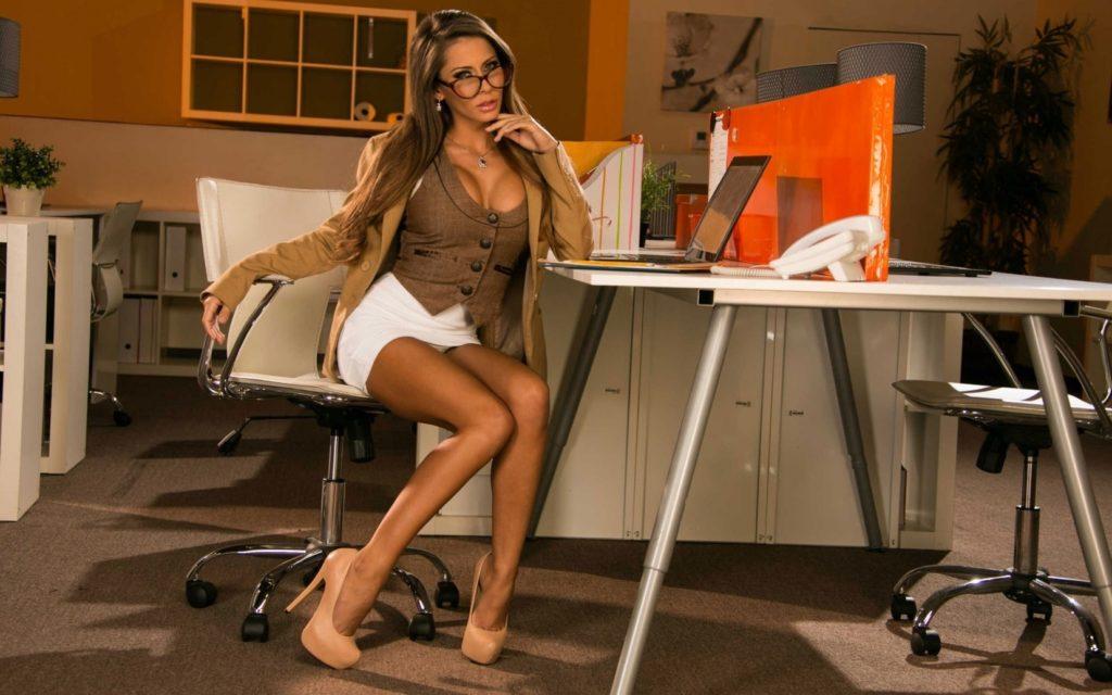 Зрелые секретарши фото в очках, сидит на офисном стуле, в белой короткой юбке, сиськи аппетитно выглядывают с декольте, туфли на высоком каблуке и платформе бежевого цвета