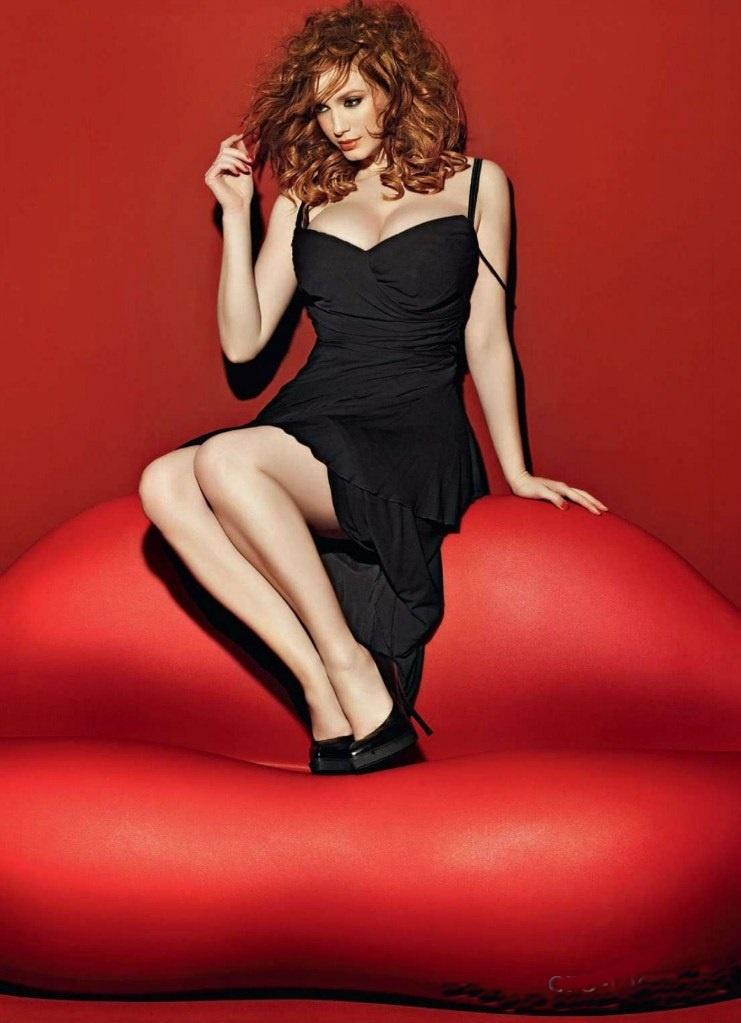 кристина хендрикс фото на диване в виде алых губ, сидит в черном платье и туфлях на каблуке