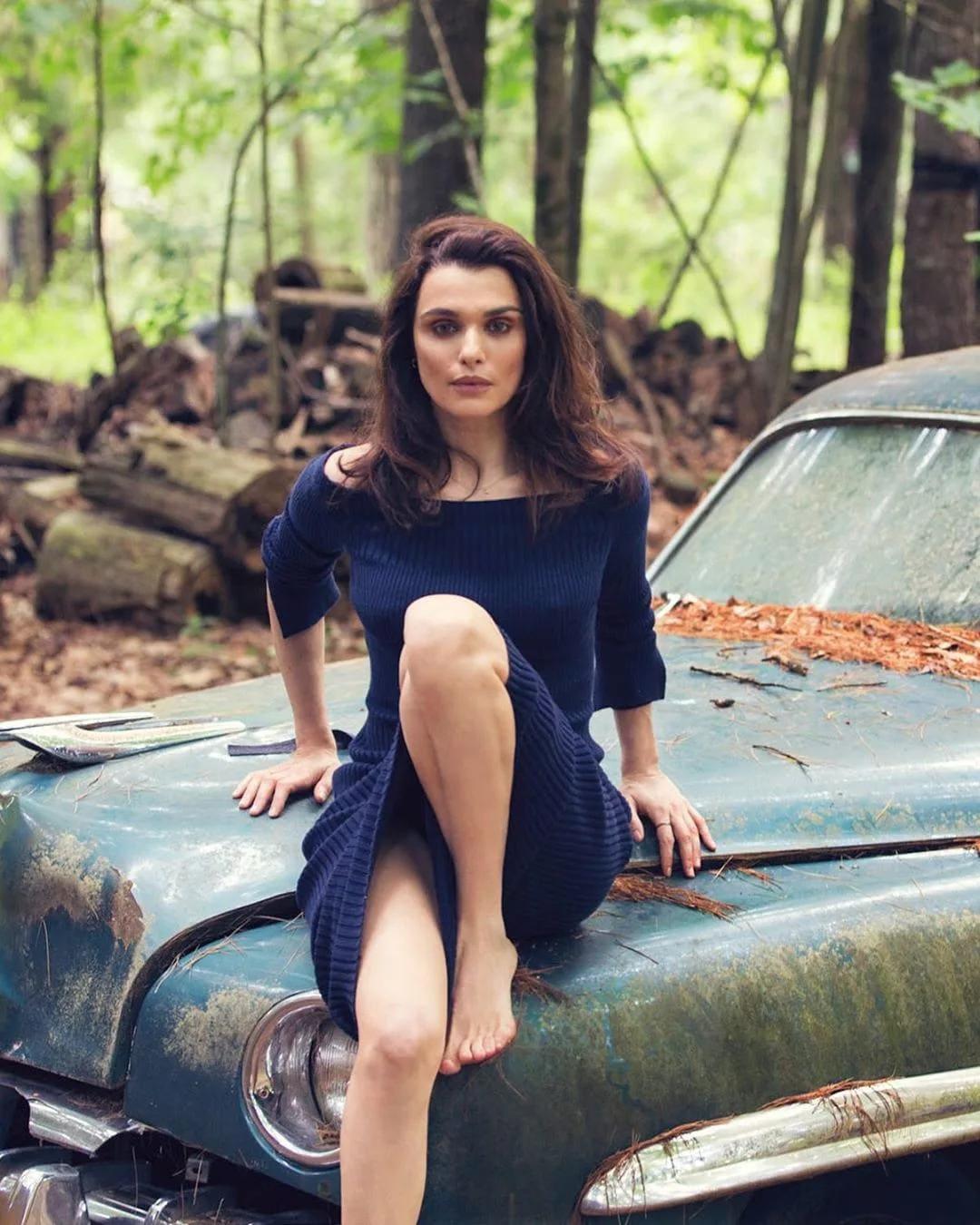 Рэйчел Вайс фото горячие сидит в лесу в темно синем платье с длинным рукавом на ржавом автомобиле, левую ногу согнула в колене и подняла на капот, босая
