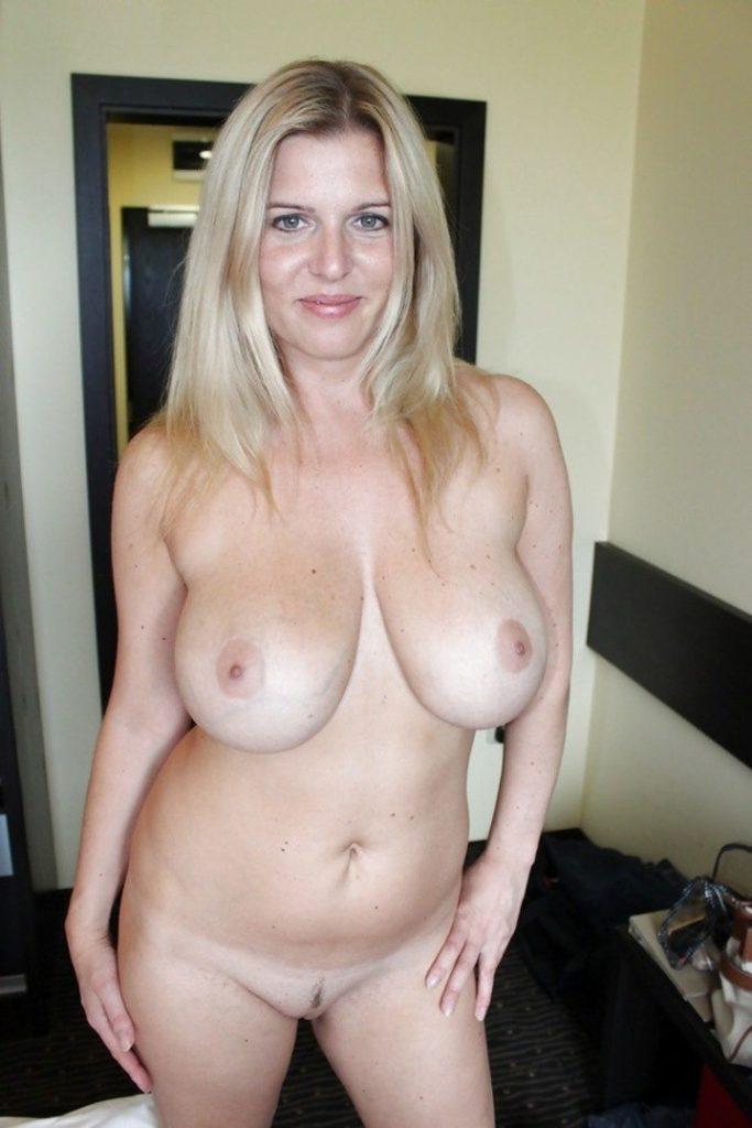 Голая зрелая блондинка стоит в коридоре мило улыбаясь, большие сиськи торчат, волосы распущены, интимная стрижка на пизде