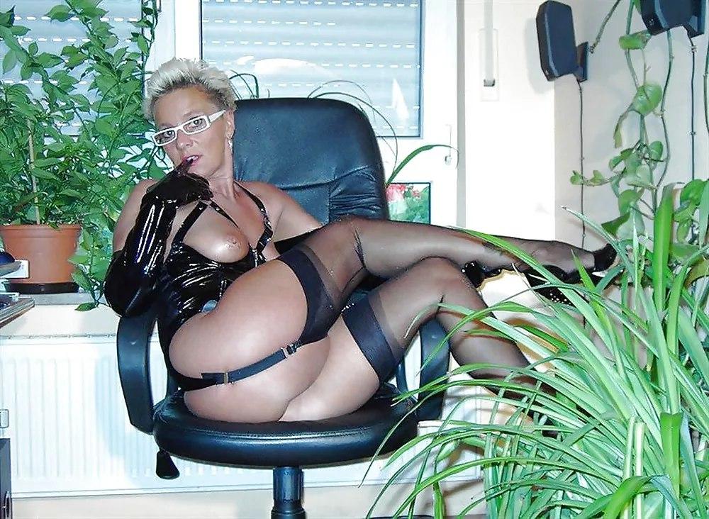 Зрелая полуголая в латексе в очках сидит в кресле ножки в чулках