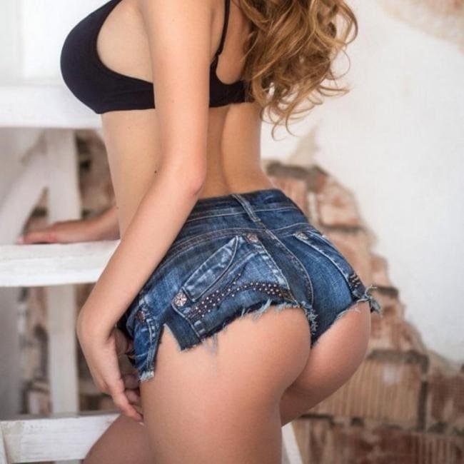 Без лица, вид сзади крупным планом попы в коротких джинсовых шортах и бюстике
