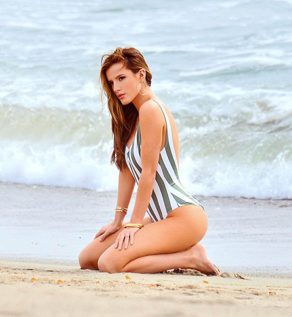 Белла Торн фото в сплошном полосатом купальнике сидит на коленях на берегу моря