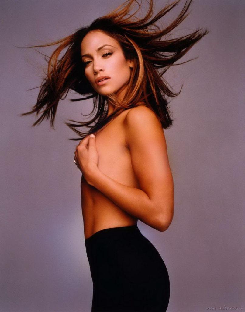 Дженифер Лопес гола фото стоит в черных обтягивающихся брюках, рукой прикрыла сиськи, вид сбоку волосы развиваются