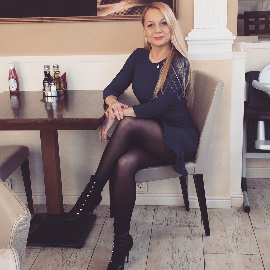 Красивая блондинка в короткой юбке сидит за столом колготки полусапожки