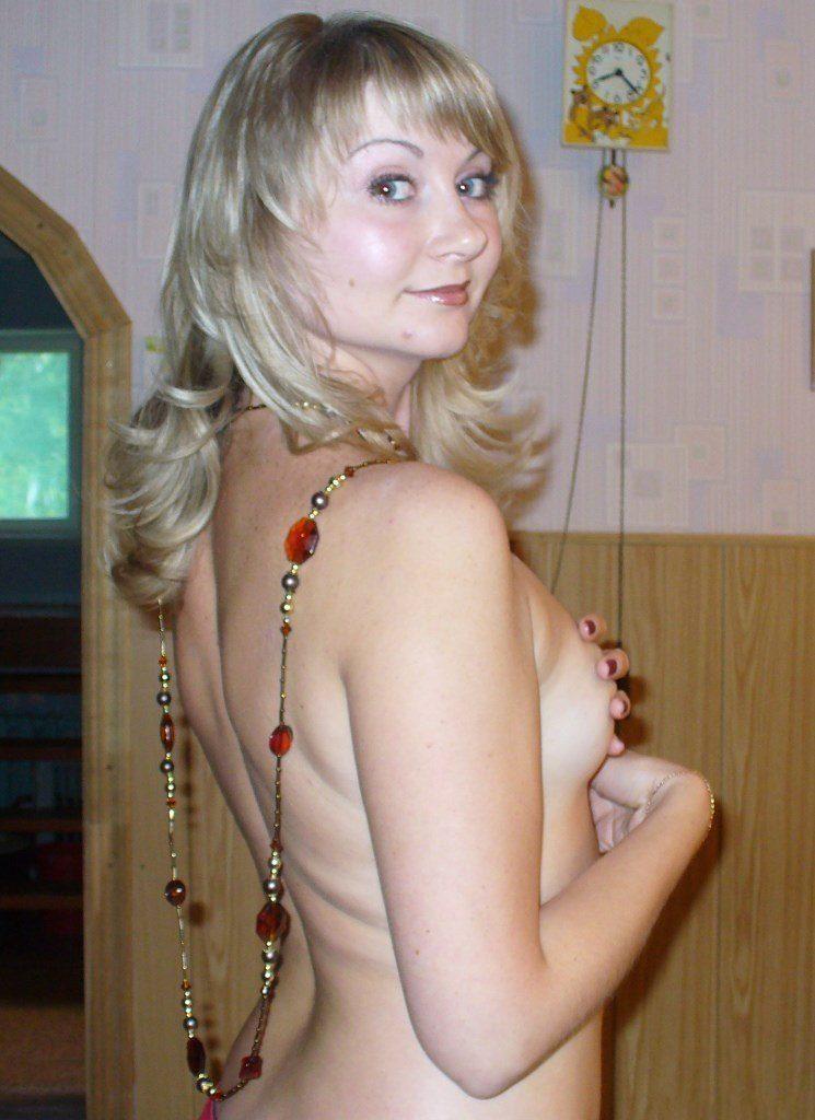 Голая блондинка с бусами вполоборота