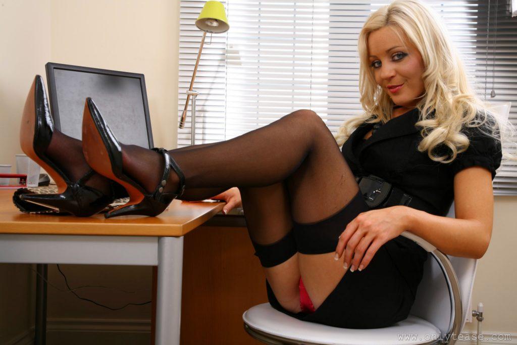 Секретарши фото чулки, блондинка сидит на стуле ноги задрала на стол, юбка короткая видны красные трусики