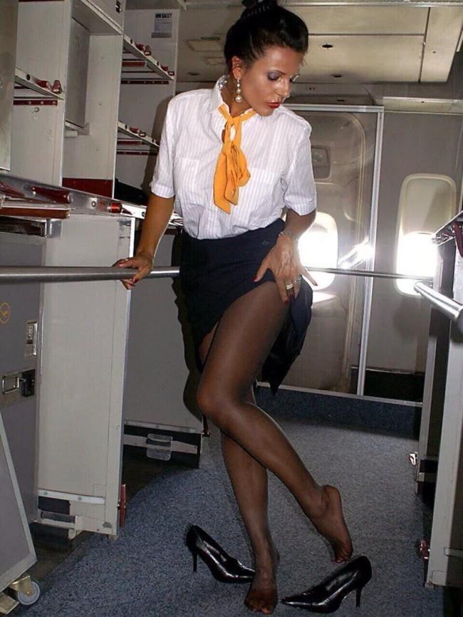 Стюардесса в самолете стоит в черных колготах, юбку задрала сняла туфли
