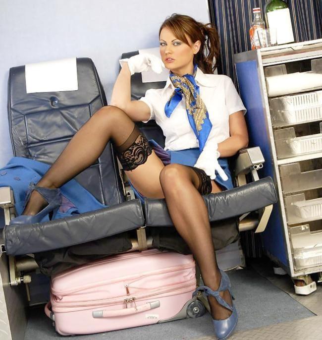 Стюардессы в черных чулках, белых перчатках сидит в кресле расставив ноги