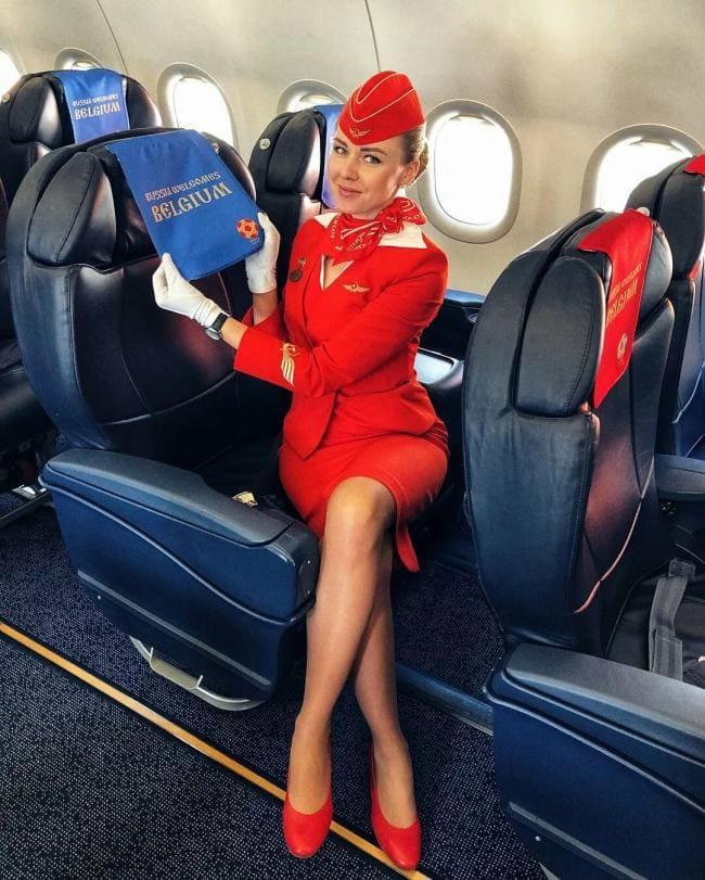 Стюардессы фото красивая в красной униформе в белых перчатках сидит в самолете
