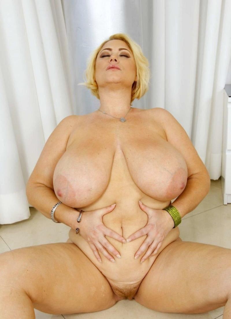 голые зрелые женщины с большими сиськами сидит на полу раздвинула ноги в сторону показывает свою волосатую пизду, руки держит на животе, голову немного подняла вверх