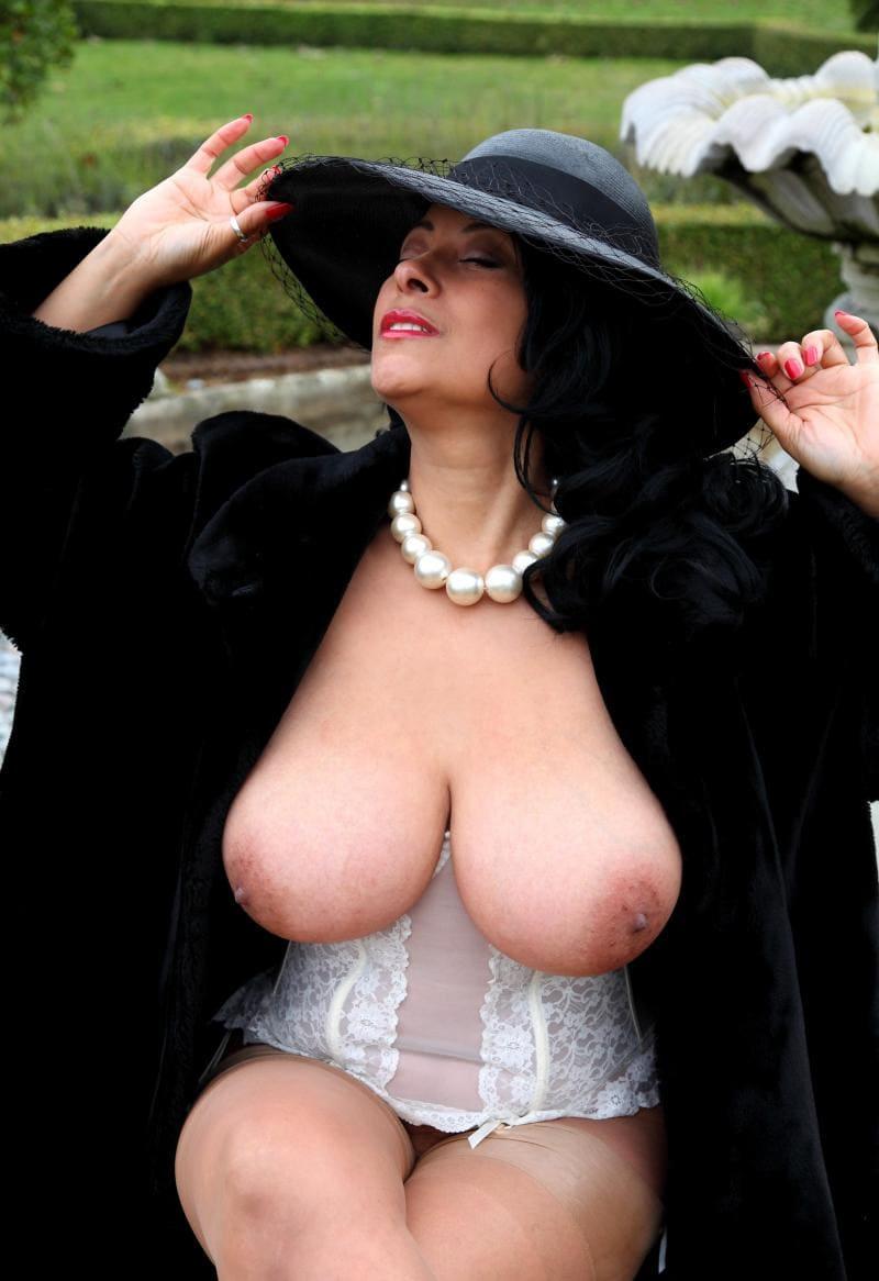 зрелые женщины с большими сиськами дама в шляпе с большими полями с бусами на шее расстегнула пальто, сидит нога на ногу