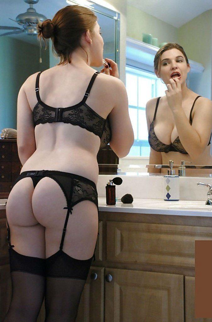 В черном нижнем белье, чулки на поясе стоит возле зеркала красит губы