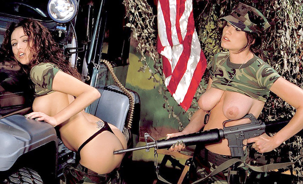 Две девушки в военной форме с голыми сиськами стоят у джипа, одна спустила брюки и нагнулась раком, другая тычет ей в ягодицу стволом автомата на фоне американского флага