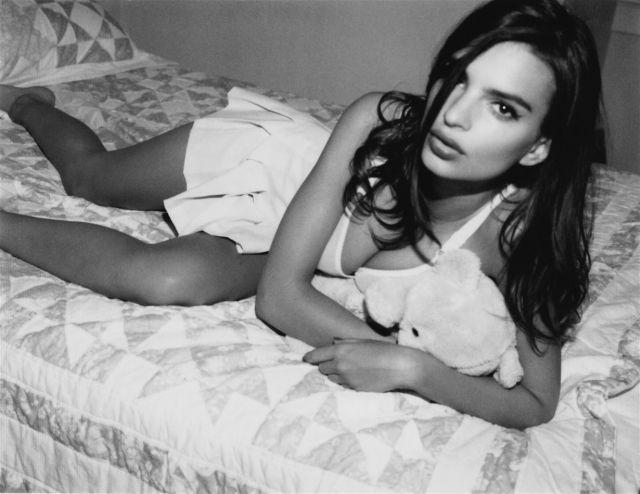 Эмили Ратаковски на кровати лежит в белой мини юбке на боку держа плюшевого мишку подмышкой, черно белое фото