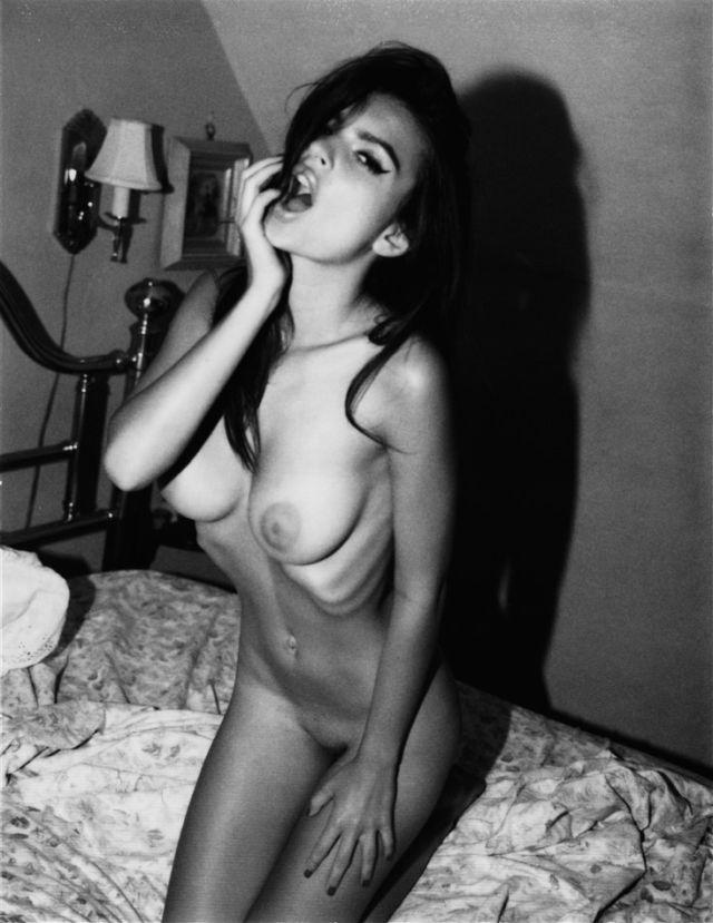 голая Эмили Ратаковски на коленях на кровати стоит, рот открыла сексуально пальчиками водит, черно белое фото