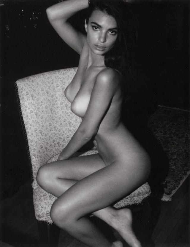 голая Эмили Ратаковски сидит на кресле подогнув ножки, правой рукой держит волосы на голове, черно белое фото