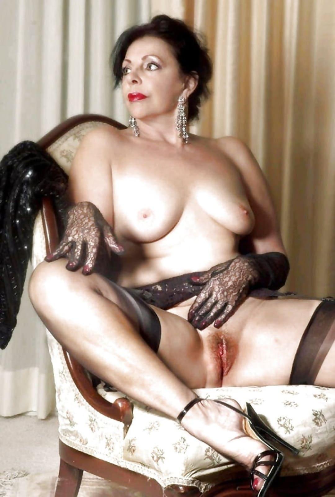 Эротика шикарная зрелая дама с голой небольшой грудью сидит в капроновых черных чулках в кресле раздвинула ноги засветила свою пизду с интимной стрижкой, открытые босоножки на каблуке, на руках короткие кружевные черные перчатки, в ушах длинные серьги