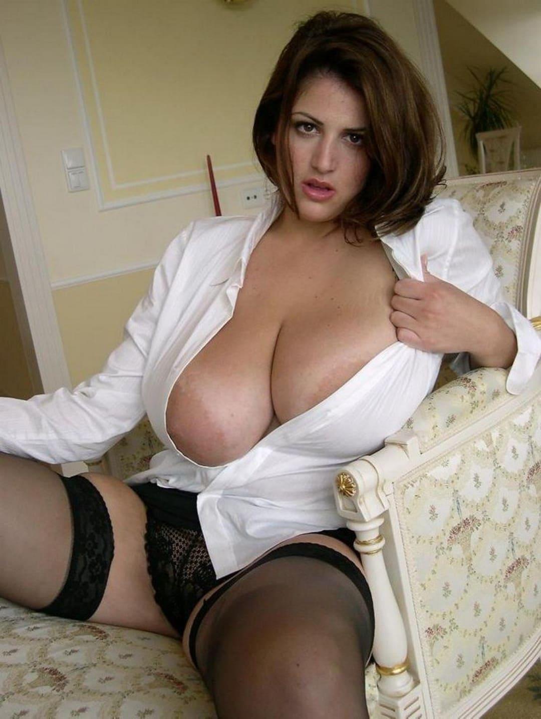 Фото эротики зрелых женщин шикарной зрелой брюнетки с большими сиськами в расстегнутой белой рубашке, черных трусах и чулках сидит в кресле раздвинула ноги