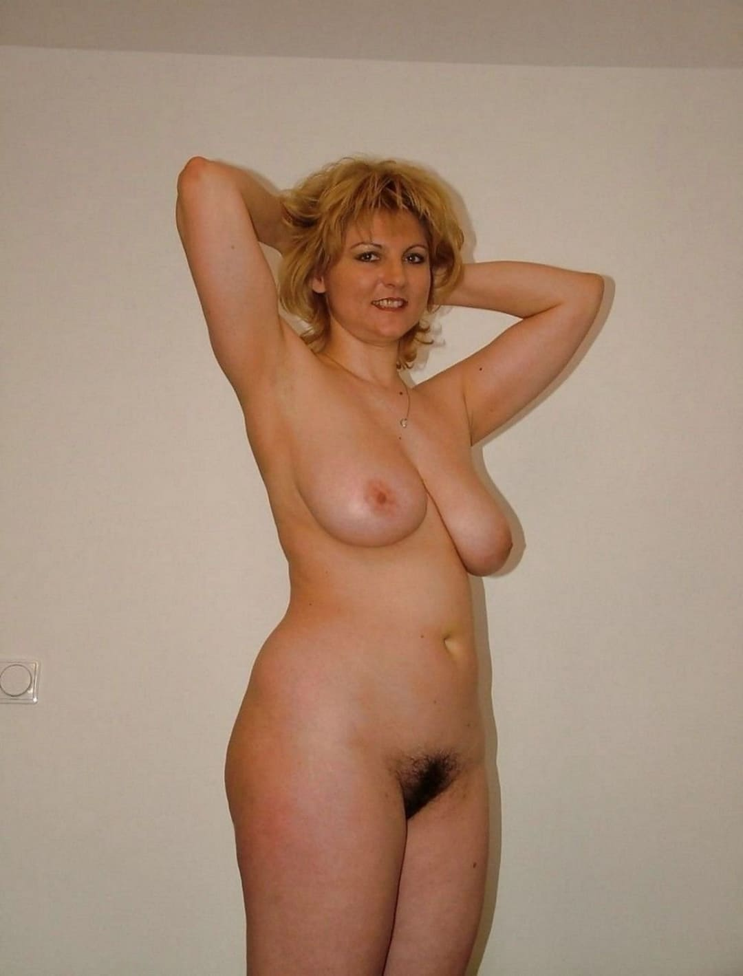 эротика фото голых зрелых женщин блондинка стоит подняв руки на голову, оголив подмышки, волосатая пизда