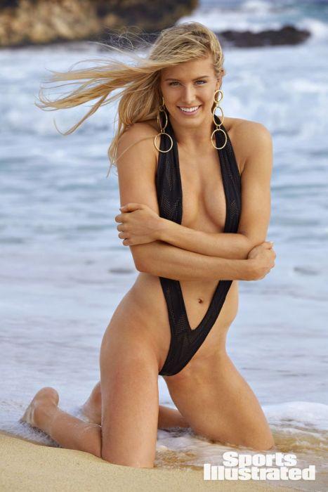 теннисистка Эжени Бушар в купльнике стоит на коленях на пляже, обнимает себя руками, приятно улыбается, в ушах серьги с большими кольцами