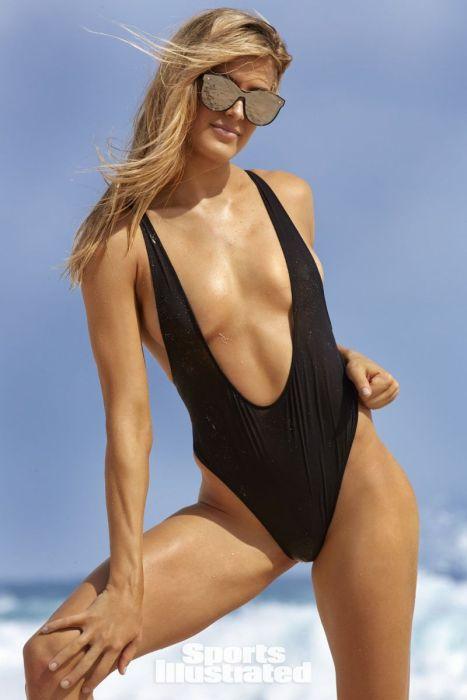 теннисистка Эжени Бушар в купльнике стоит на берегу моря в солнцезащитных очках, правой рукой тянется к колену, левую руку положила на бедро