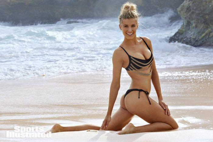 Эжени Бушар в купальнике сидит на коленях на пляже, волосы собраны, повернулась в полоборота и красиво улыбается
