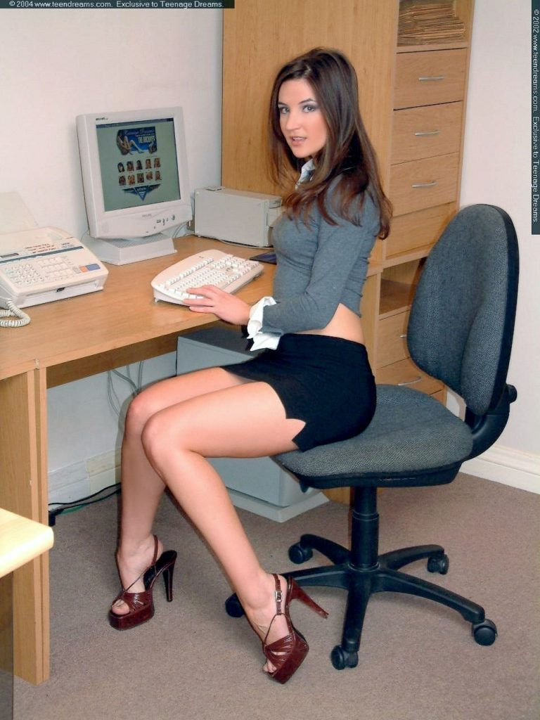 Секретарши в юбке фото сидит на стуле, короткая черная юбка с небольшими разрезами показывает красивые ножки в босоножках на высоком каблуке