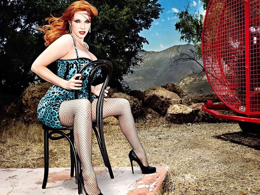 Кристина Хендрикс в черных чулках в крупную сетку сидит на стуле на каменном помосте в горах, перед ней стоит большой вентилятор и дует, волосы трепещутся от ветра