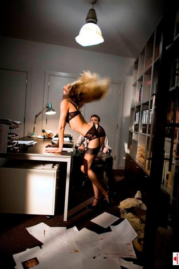 Фото эротика секретарши в нижнем черном белье, чулках на поясе исполняет танец перед боссом