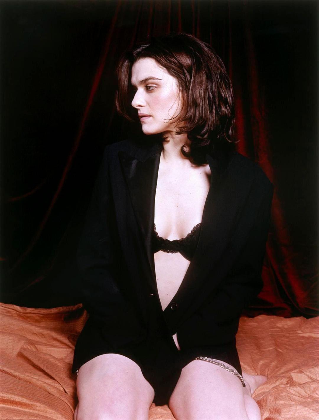 Рэйчел Вайс фото сидит на кровати в расстегнутом черном пиджаке выглядывает бюстик с сиськами, голова повернута набок, задумчивый взгляд