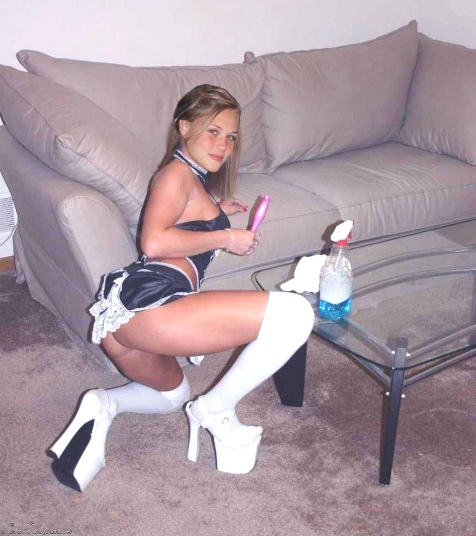 Молоденькая полуголая горничная стоит на колене возле дивана в белых гетрах босоножках на огромной платформе
