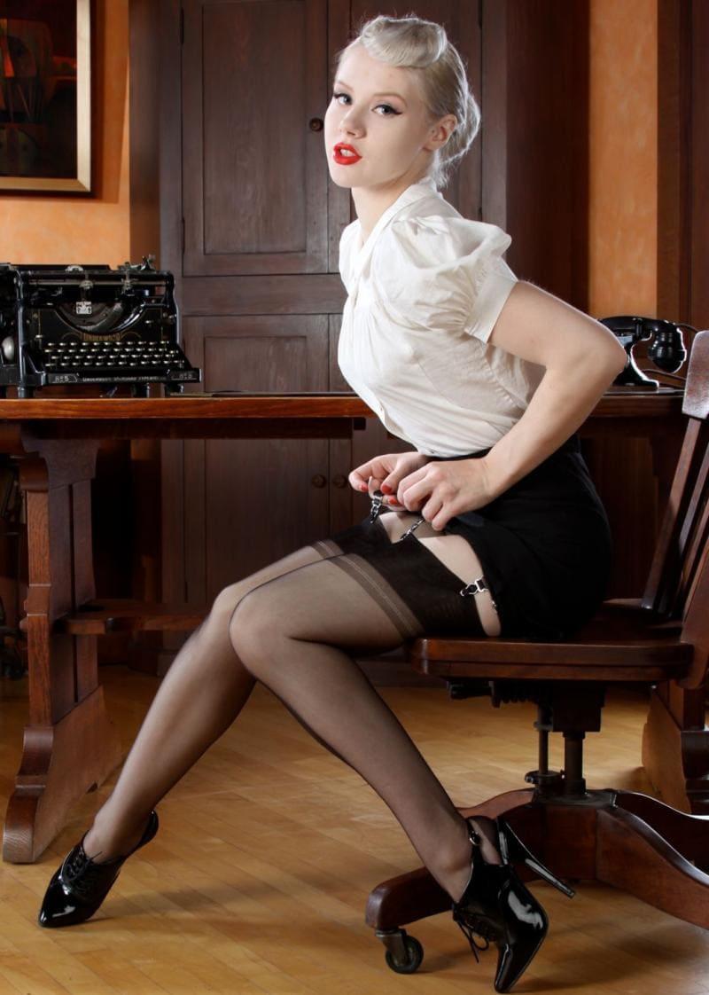 Красивая блондинистая секретарша фото ретро в чулках на поясе, короткой юбке, белой кофточке с рукавами фонариком, туфлях на высоком каблуке, яркая помада на губах
