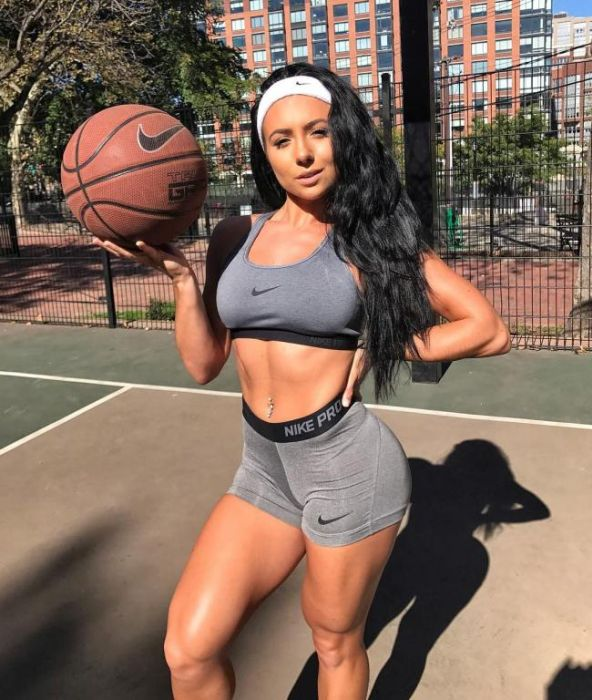 В спортивных шортах, коротком топике с мячом стоит