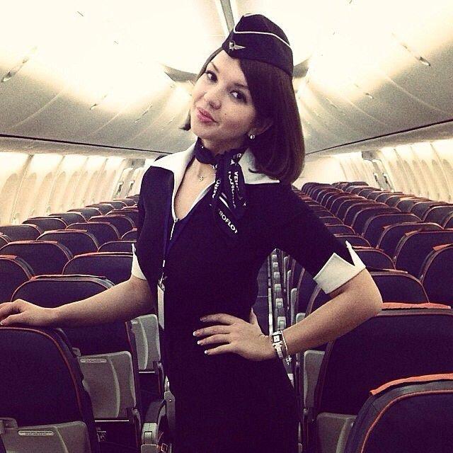Стюардесса в самолете стоит рука на поясе, улыбается
