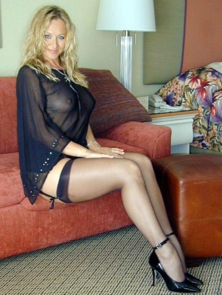 красивые зрелые женщины фото эротика блондинка с распущенным волосом сидит на красном диване в черном коротком пеньюаре, чулках на каблуках
