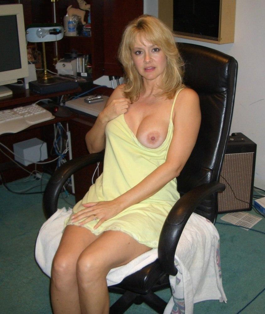 красивые зрелые женщины фото эротика блондинка сидит в кожаном кресле в желтом пеньюаре, немного отодвинула его в сторону оголив одну грудь