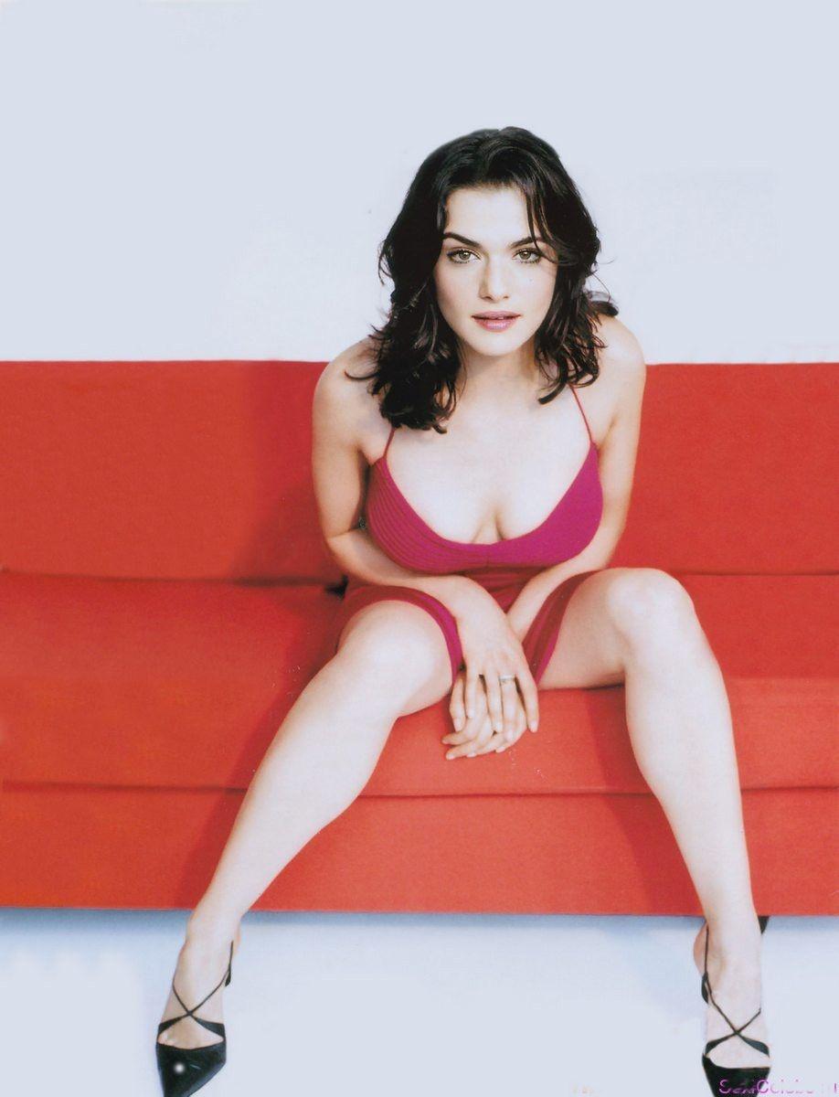 Рэйчел Вайс фото горячие на красном диване в коротком ярком бордовом платье с глубоким декольте сидит в туфлях на каблуках. ноги раздвинула